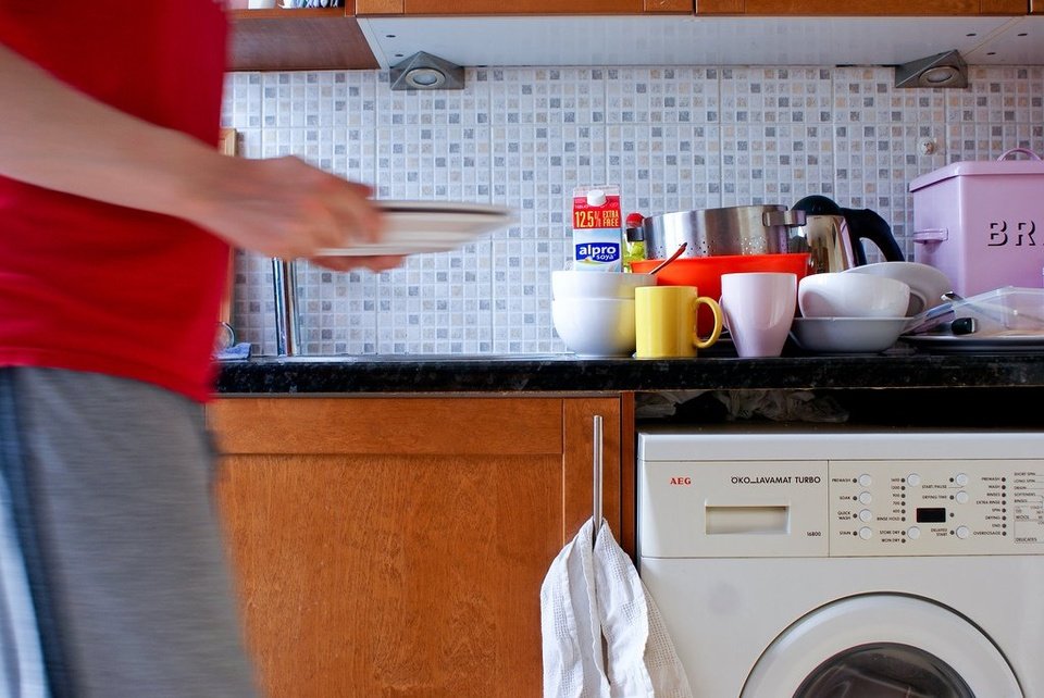 Man Carrying Dishes In Kitchen - Teen Rehab