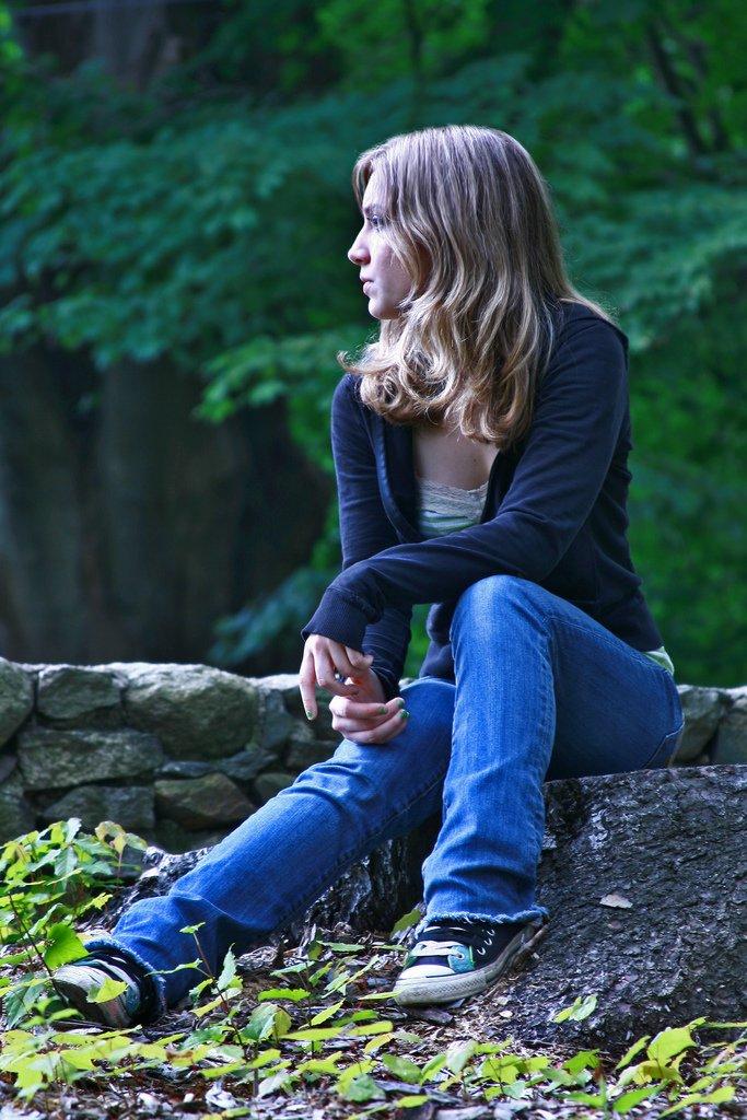 Teenage Girl Sitting On Rock Looking Away - Teen Rehab