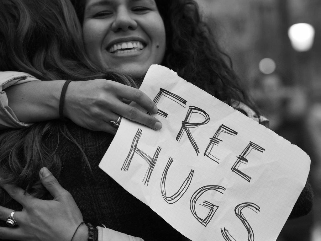 woman free hugs sign black white