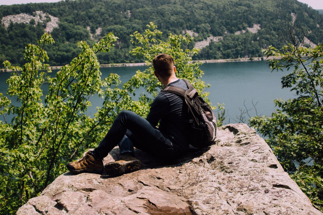 calm teen sitting on rock