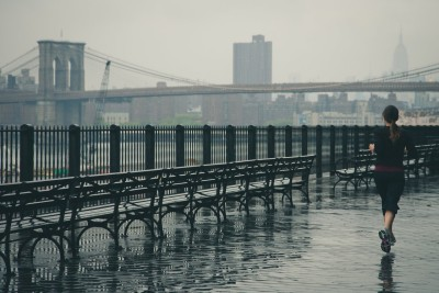 woman jogging rain new york nyc bridge