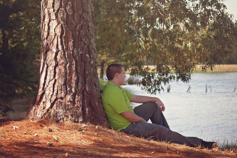 teen boy sitting tree