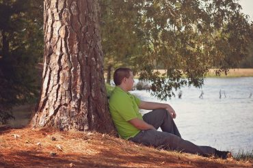 teen boy sitting tree