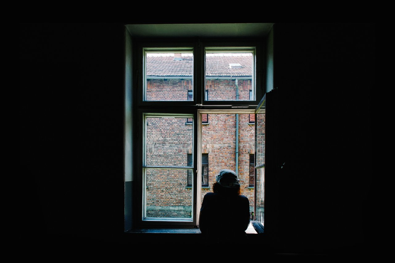 teen staring out window alone