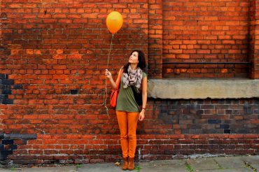 woman brick wall balloon