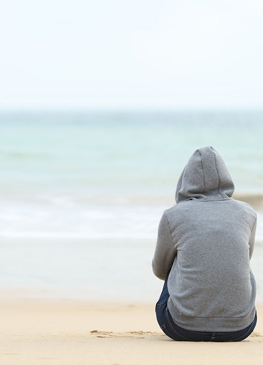 Teen Rehab - Homepage Hero Image of Person in Hoodie on Beach