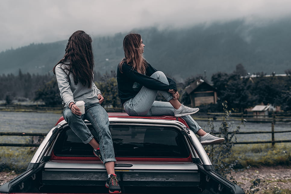 Two young women sit on top of the cab of a pickup truck, looking off into the distant cloudy mountains. The girl on the left holds a to-go coffee cup, and the other braces her knee against herself.