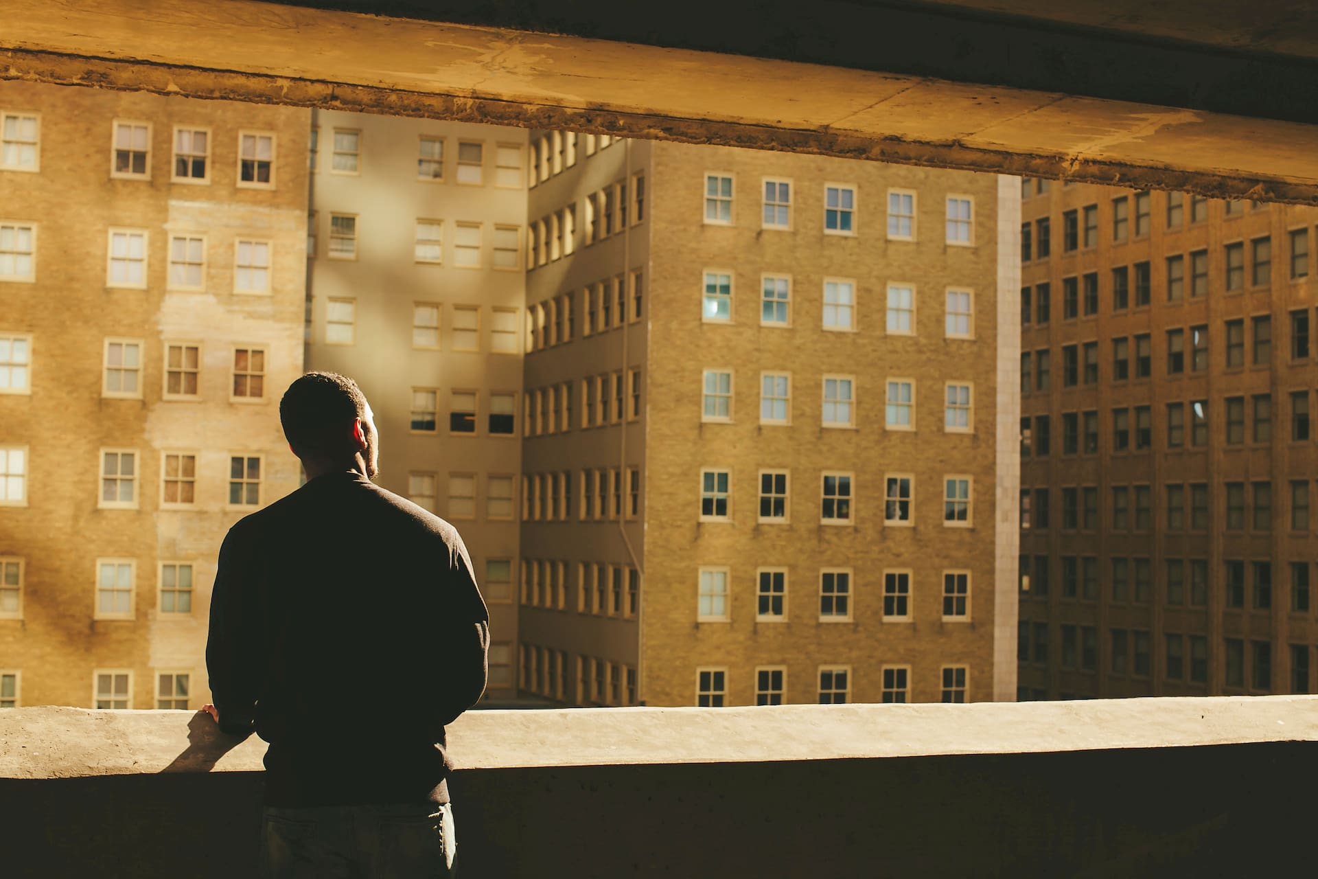 We stand behind a man on a concrete balcony as he looks into the sunlight on the buildings in the distance.